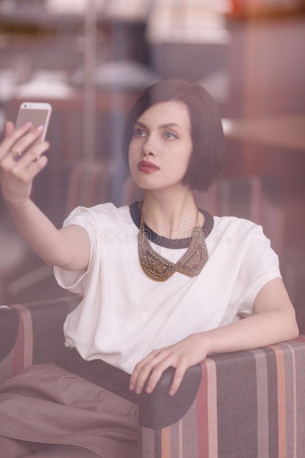 Selfie. Woman behind the window taking selfie sitting in cafe royalty free stock images