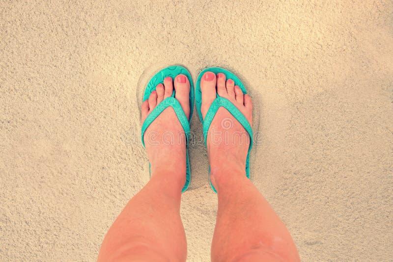 Selfie of woman feet wearing flip flops on a beach. Vintage process royalty free stock image