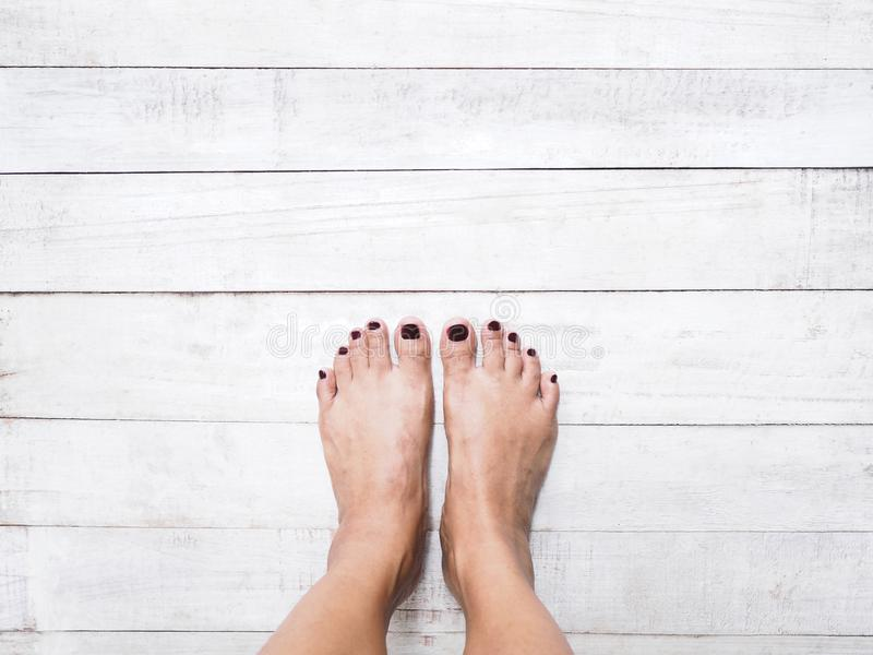 Selfie woman feet isolated on wood background. royalty free stock image