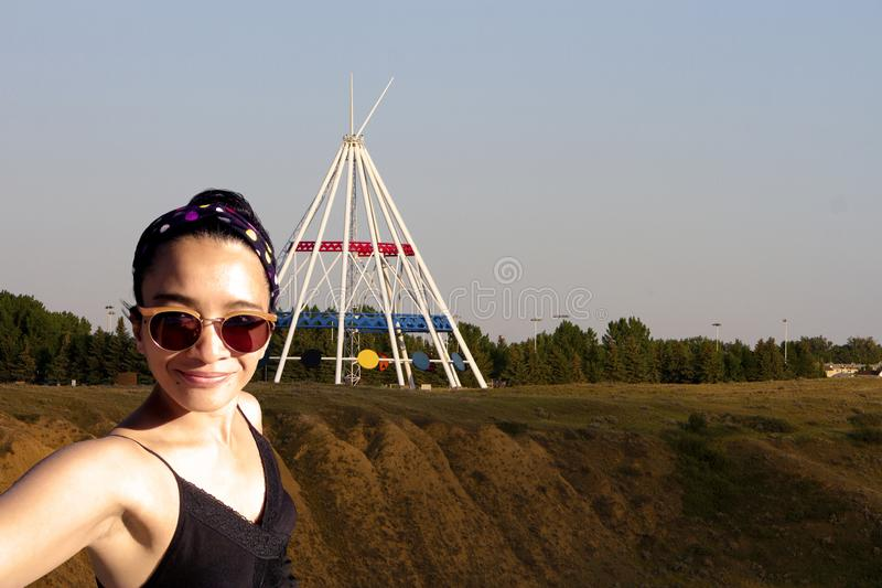 Selfie Woman Medicine Hat. One young adult woman taking a selfie photo in Saamis Teepee Medicine Hat, Alberta, Canada on holiday travel vacation freedom royalty free stock photo