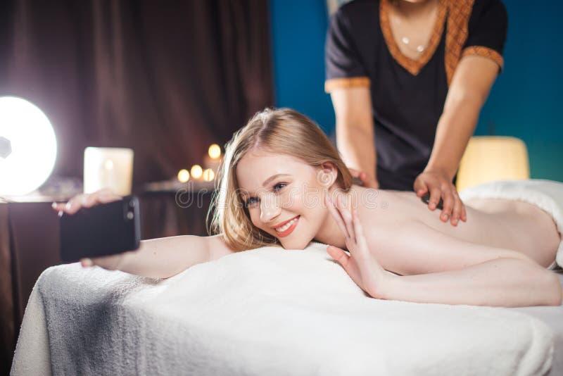 Selfie wtaking de jeune jolie femme au salon de station thermale tout en obtenant le massage arrière photographie stock