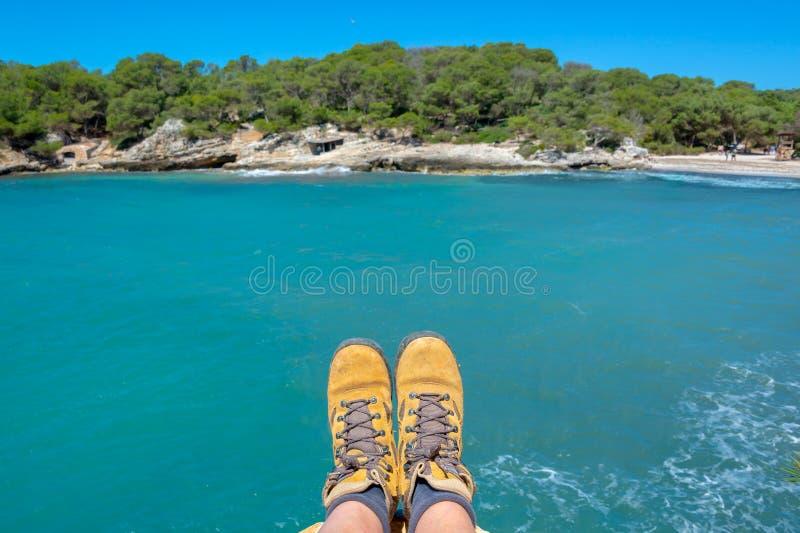 Selfie wycieczkować buty, śródziemnomorski błękitne wody tło w Menorca, Balearic wyspy Hiszpania zdjęcie stock