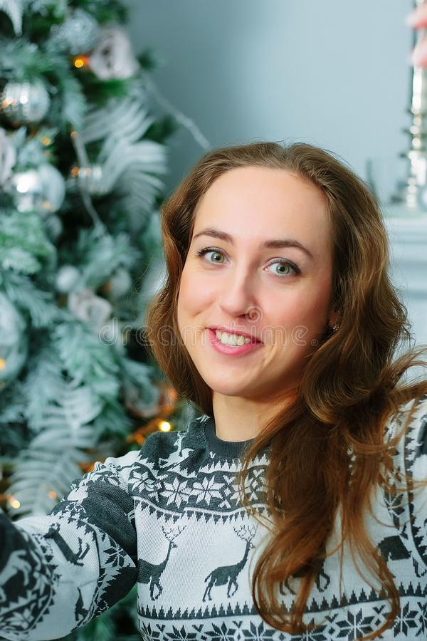Selfie of young beautiful woman with the christmas tree on background. Selfie of young beautiful woman with the christmas tree on background - christmas and new royalty free stock photo