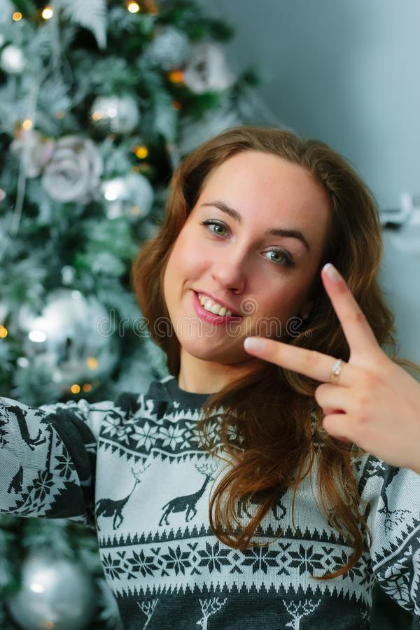 Selfie of young beautiful woman with the christmas tree on background. Selfie of young beautiful woman with the christmas tree on background - christmas and new royalty free stock photography