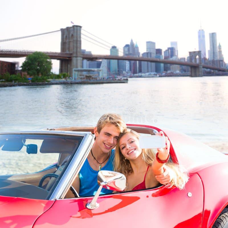 Selfie young couple convertible New York Brooklyn Bridge stock photo