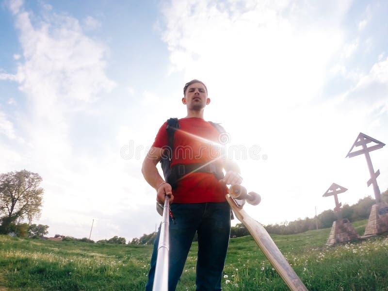 Selfie z longboard, młody człowiek w czerwonej koszula na tle jaskrawy słońce obraz stock