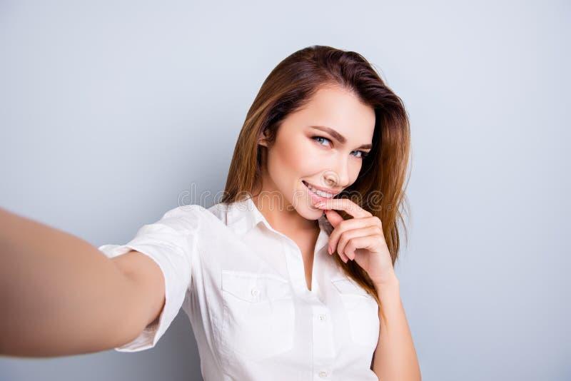 Selfie-Zeit! So heiß und recht! Attraktive junge Dame macht ein selfie auf der Kamera, flirty und spielerisch In der Freizeitklei lizenzfreie stockfotografie