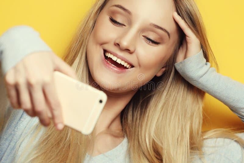 Selfie-Zeit Lächelnde blonde Frau der Junge, die selfie auf gelbem Hintergrund tut stockfotos