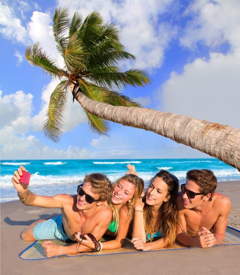Selfiegroep toeristenvrienden in een tropisch strand stock afbeelding