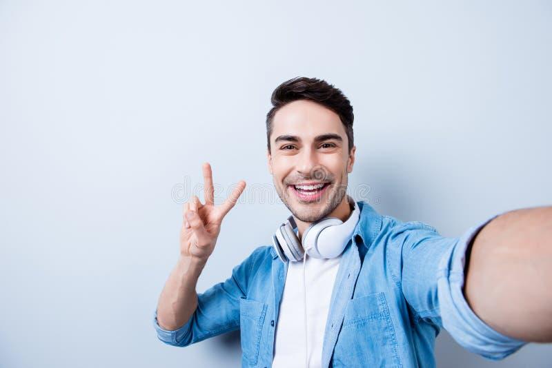 Selfiemanie! De knappe glimlachende jonge brunete mens met stoppelveld is stock afbeelding