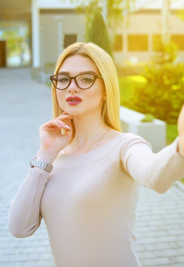 Selfieportret van een mooi meisje in een beige kleding en glazen in de loop van de dag in openlucht Het model stelt voor royalty-vrije stock afbeeldingen