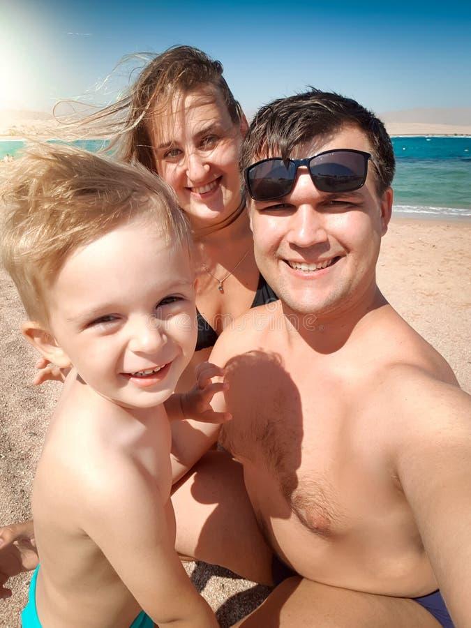 Selfieportret van gelukkige glimlachende moeder, vader en weinig zoon die selfie foto op overzees strand maken familie het ontspa stock fotografie