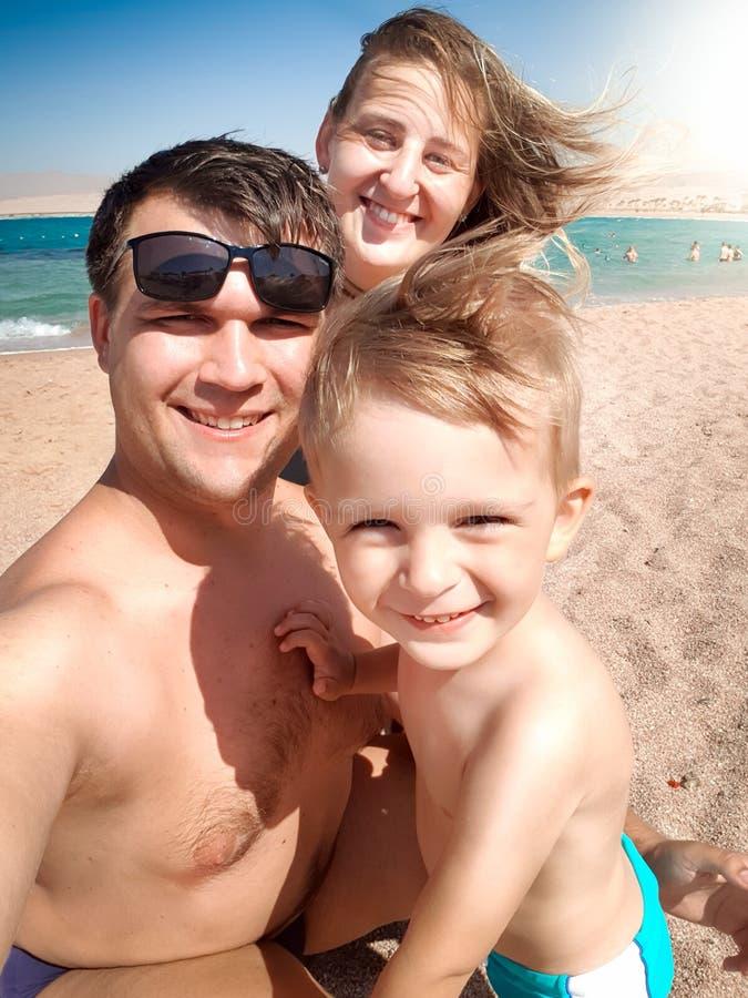 Selfieportret van gelukkige glimlachende vrolijke familie op het overzeese strand bij zonnige winderige dag r royalty-vrije stock afbeeldingen