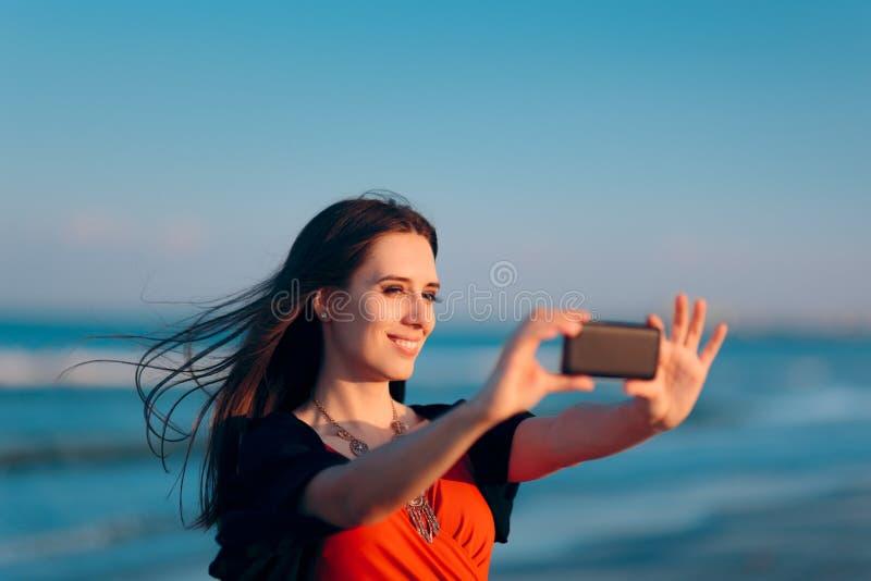Selfies de prise de touristes femelle au coucher du soleil par la mer photos stock