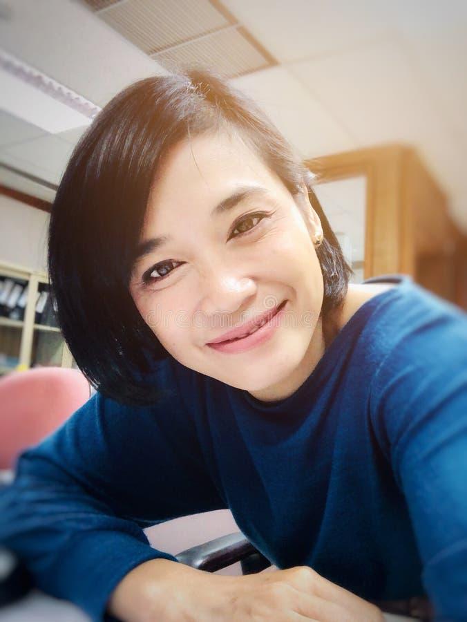 Selfies do sorriso da menina ou da mulher asiática que sorriem no escritório e que olham a câmera imagens de stock royalty free