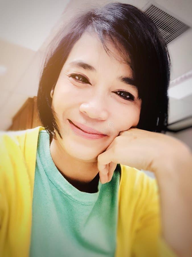 Selfies du sourire de fille ou de la femme asiatique souriant au bureau et regardant la cam?ra image stock