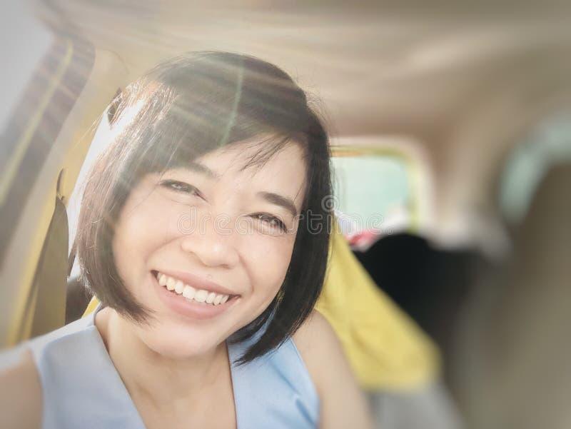 Selfies du sourire de fille ou de la femme asiatique souriant dans la voiture et regardant la caméra photo libre de droits