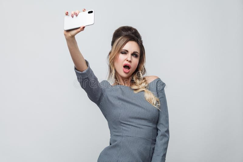 Selfietijd! Gelukkig mooi blogger jong meisje die in grijze kleding met vlecht bij de hoofd status dragen, die met sexy open mond royalty-vrije stock afbeelding