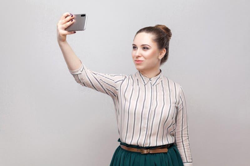Selfietijd! Het portret van het gelukkige aantrekkelijke bloggervrouw dragen in gestreept overhemd die, het houden telefoneert en stock afbeelding