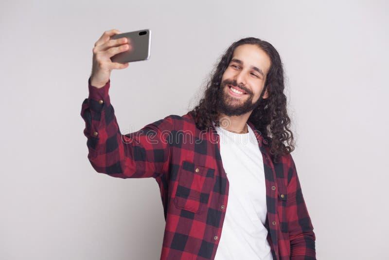 Selfietijd! Knappe jonge mens in rood geruit overhemd en lang stock afbeelding