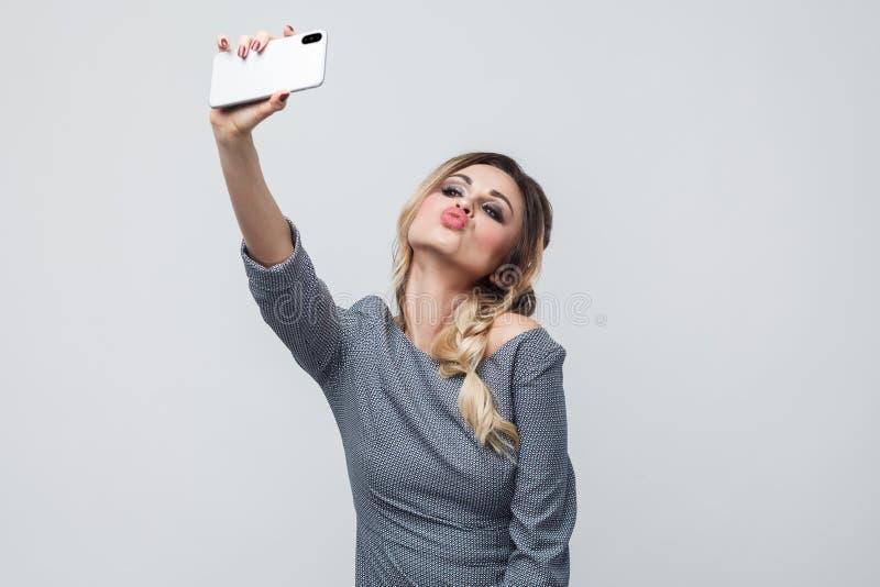 Selfietijd! Selfportrait die van het gelukkige mooie bloggertiener dragen in grijze kleding met vlecht bij de hoofd status, lucht stock afbeeldingen