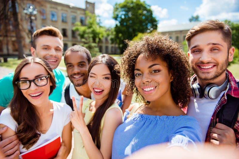 Selfietijd! Zes internationale studenten met het richten van glimlachen zijn stock afbeelding