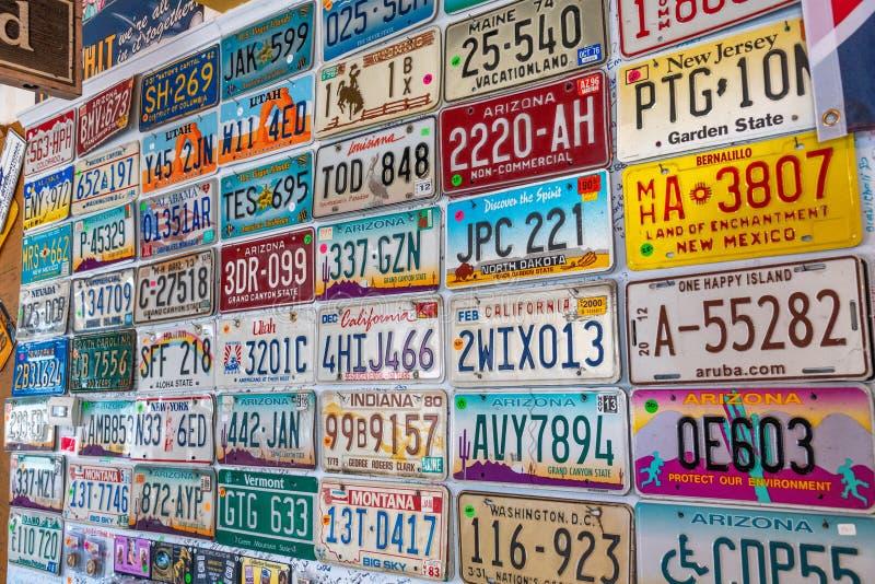 SELIGMAN, AZ - CZERWIEC 29, 2018: Starzy samochodów talerze wykładający na ścianie Se zdjęcia stock