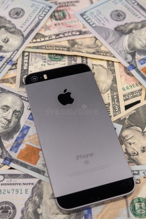 Selinsgrove, PA, USA - 31. März 2019: Ein Apple-iPhone sitzt auf einen Stapel von Währung Vereinigter Staaten lizenzfreie stockfotos