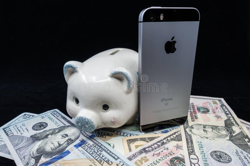 Selinsgrove, PA, usa - Marzec 31, 2019: Jabłczany iPhone siedzi na górze stosu Stany Zjednoczone waluta fotografia stock