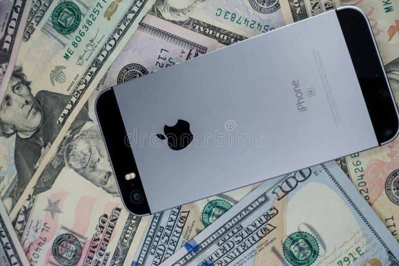 Selinsgrove, PA, usa - Marzec 31, 2019: Jabłczany iPhone siedzi na górze stosu Stany Zjednoczone waluta obraz stock