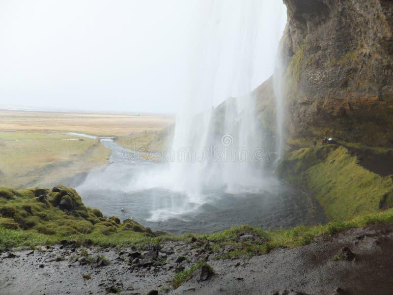 Seljalandfoss vattenfall i Island som bakifrån beskådas det fallande vattnet royaltyfri bild