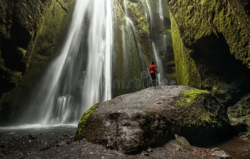 Seljalandsfoss, Исландия - уединённая персона в красном цвете исследует Gljufrafos стоковые фото