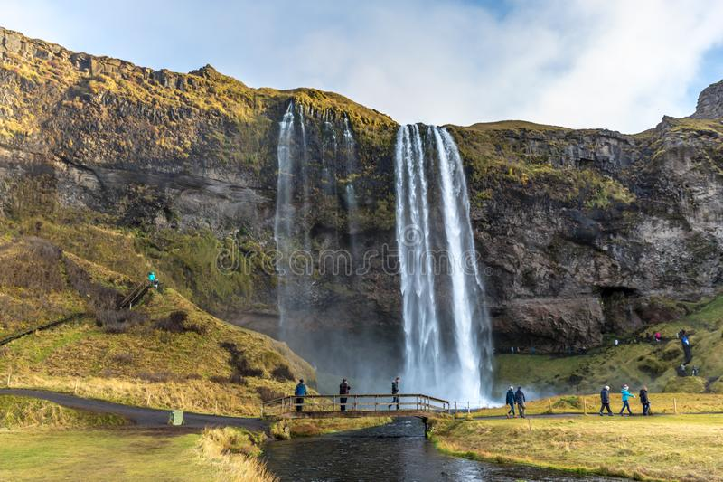 Seljalandsfoss, Iceland - Oct 22th 2017 - Tourists enjoying the Seljalandsfoss fall in a overcast day in Iceland. royalty free stock image