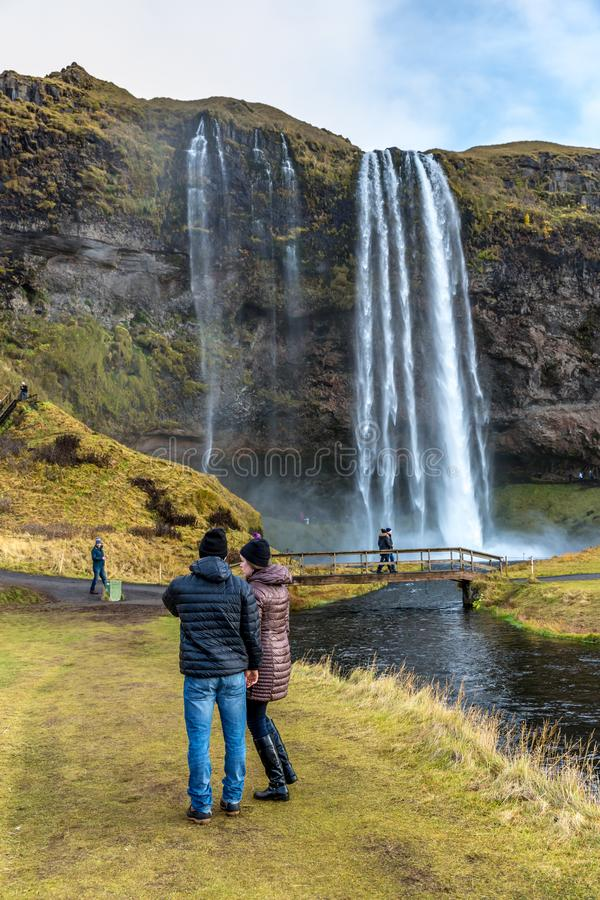Seljalandsfoss, Iceland - Oct 22th 2017 - Young couple enjoying the Seljalandsfoss fall in a overcast day in Iceland. royalty free stock photos