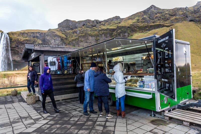 Seljalandsfoss Island - Oktober 22. 2017 - ung köpandemat i en sort av matlastbilsläpet i den Seljalandsfoss nedgången i ett mule fotografering för bildbyråer