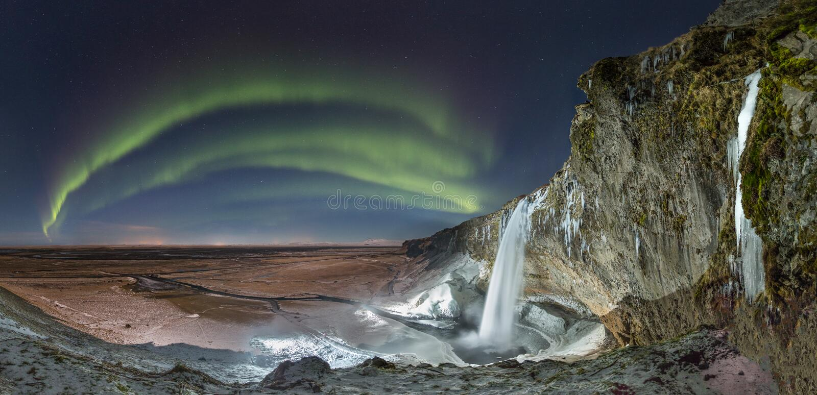 Seljalandsfoss waterfall, Iceland. A panorama of the Northern Lights dancing in the skies by Seljalandsfoss waterfall, Iceland, during winter with the moonlight royalty free stock image