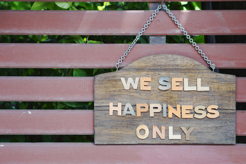 We sell happiness only signage. On timber plates and timber slat background stock image
