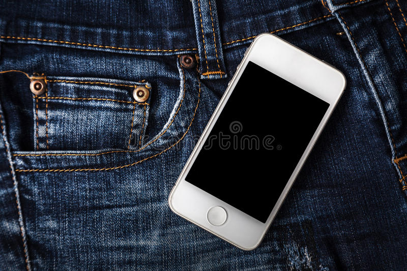 Sell online. White phone, put on old jeans concept of selling clothes online royalty free stock photos