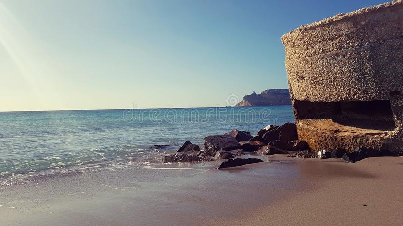 Sella del Diavolo udde som beskådas av den Poetto stranden, Cagliari, Italien royaltyfria bilder
