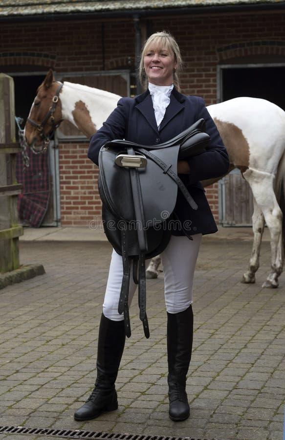 Sella della tenuta del cavaliere della donna con il suo cavallo fotografia stock