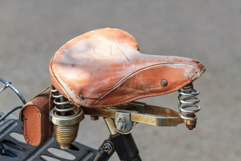 Selle en cuir de vélo de vintage avec des ressorts en métal photos stock