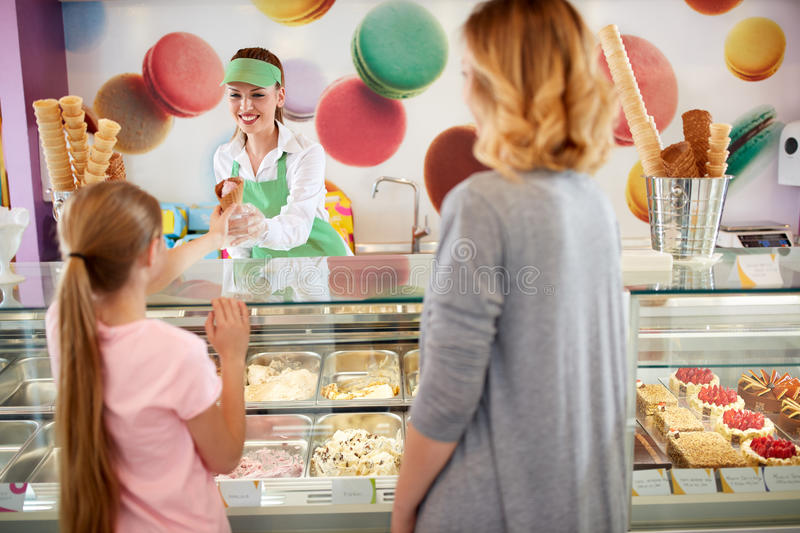 Seller in bakery gives ice cream to girl stock photography