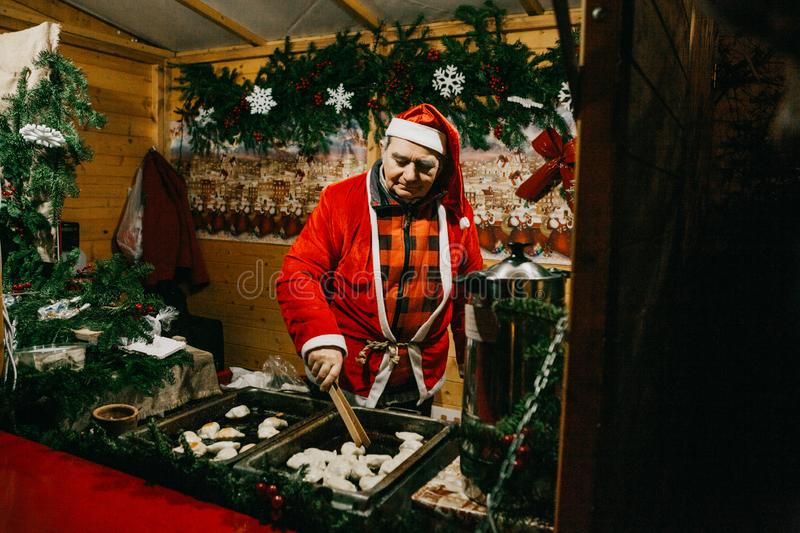 A seller dressed as Santa Claus sells fast food stock images