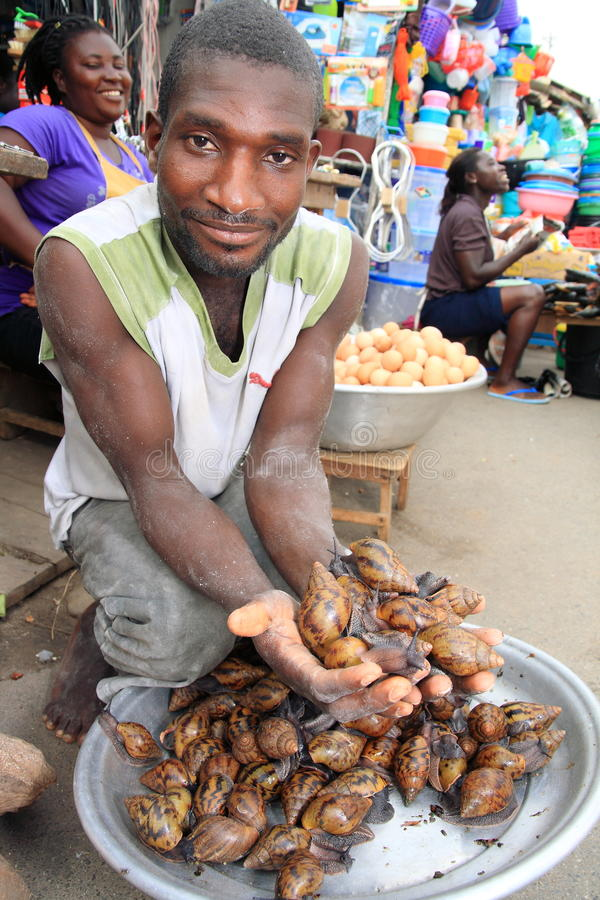 Seller of giant snails on African market. Cape Coast, one of the largest agglomeration in Ghana (Western Africa) and an important sea harbor. The market located royalty free stock photos
