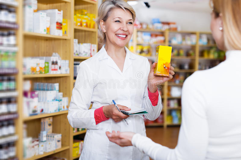 Seller helping customer to choose care products. Smiling adult seller helping customer to choose care products in specialized shop stock photos