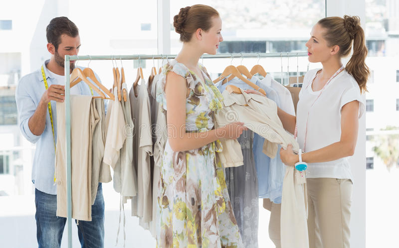 Seller helping shopper choose clothes in store stock photo