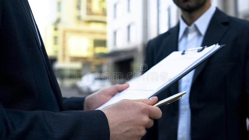 Seller looking through list, searching name of man buying auto, business deal royalty free stock photo