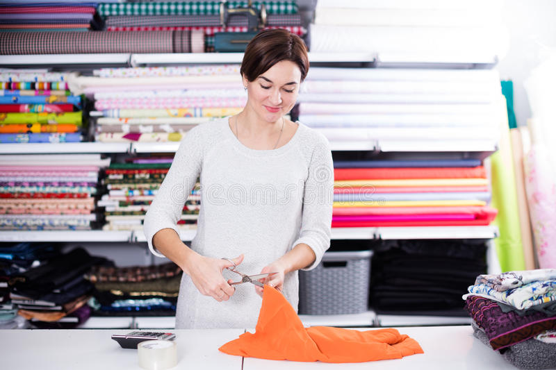 Seller measuring cloth. Young woman seller measuring square of cloth at drapery shop stock photography
