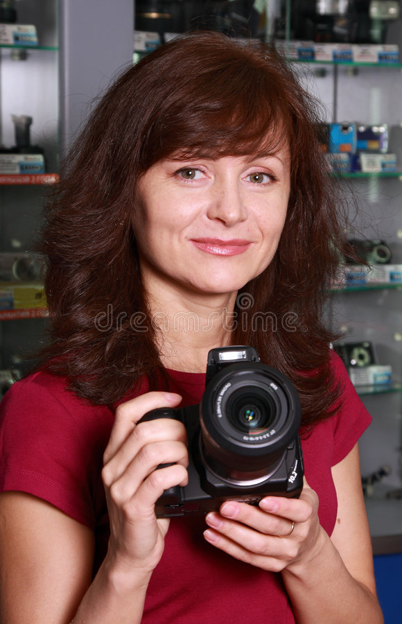 Seller photographic equipment. The woman - seller in photographic shop advertises the camera royalty free stock image