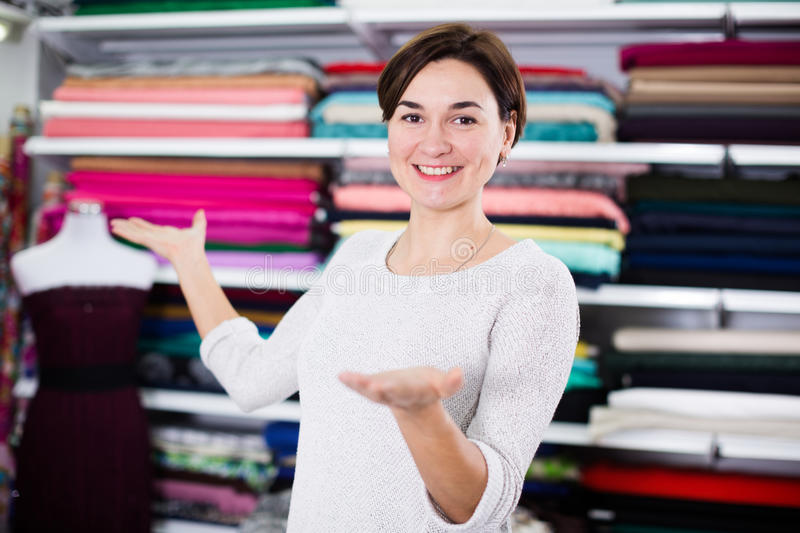 Seller showing assortment. Smiling girl seller showing wide assortment at drapery shop royalty free stock image